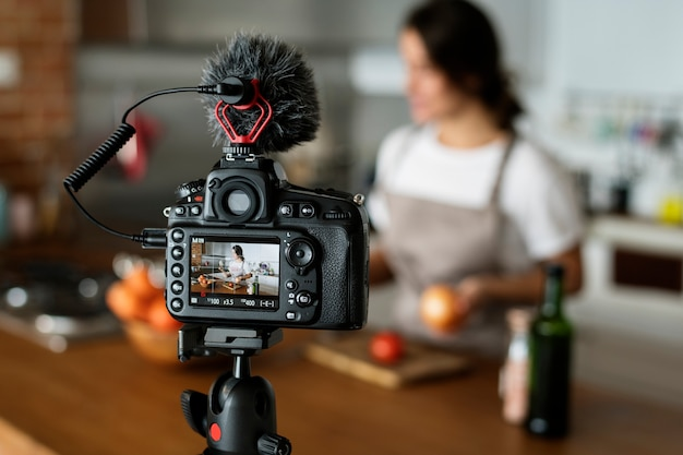 Weibliche vlogger aufzeichnung, die zu hause bezogene sendung kocht