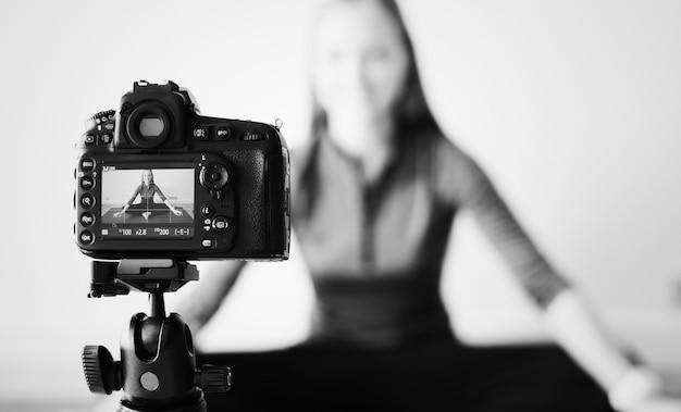 Weibliche vloggerin, die zu hause sportbezogene sendungen aufzeichnet