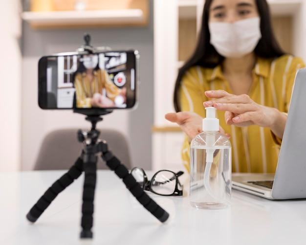 Weibliche vloggerin zu hause mit smartphone und händedesinfektionsmittel