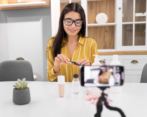 Weibliche vloggerin zu hause mit smartphone und mascara