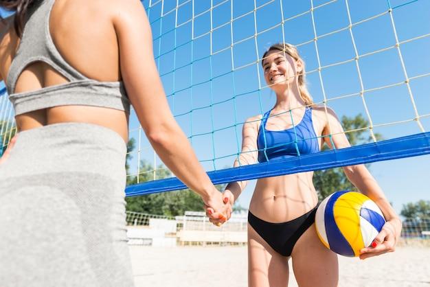 Weibliche volleyballspieler, die hände unter dem netz schütteln
