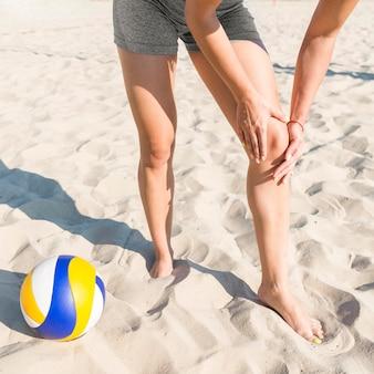 Weibliche volleyballspielerin, die ihr knie beim spielen verletzt