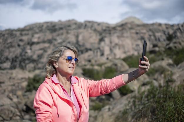 Weibliche wanderer, die ihr telefon benutzen und die schöne aussicht fotografieren