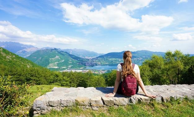 Weibliche wanderer, die sich nach dem trekking in den bergen entspannen und die aussicht vom belvedere genießen