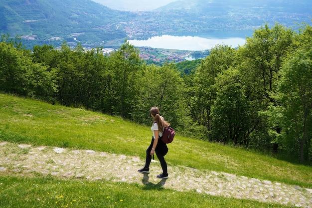 Weibliche wanderer geht den weg und schaut mit zufriedenheit von der spitze des berges auf den see