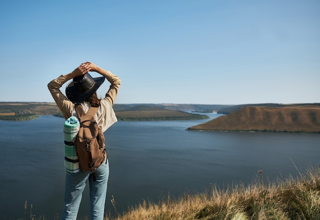 Weibliche wanderer mit rucksack, die pause auf hohem hügel machen