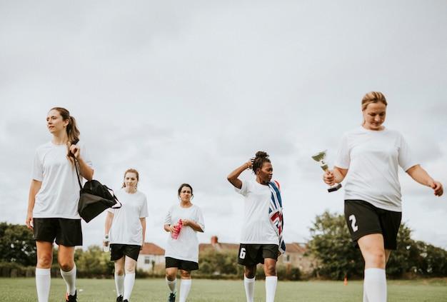 Weibliche weibliche fußballspieler, die auf ein feld gehen