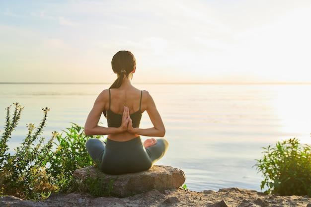 Weibliche yoga-meisterin, die sich bei yoga-übungen am strand die hände hinter dem rücken verbindet