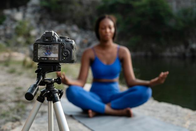 Weibliche yogalehrerin, die im freien übt