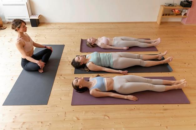 Weibliche yogalehrerin, die klasse unterrichtet Kostenlose Fotos
