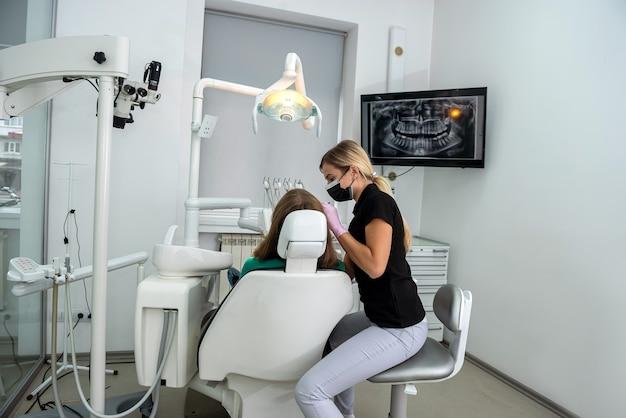 Weibliche zahnärztin bereitet sich auf zahnärztliche untersuchung junge patientin vor. gesunde zähne