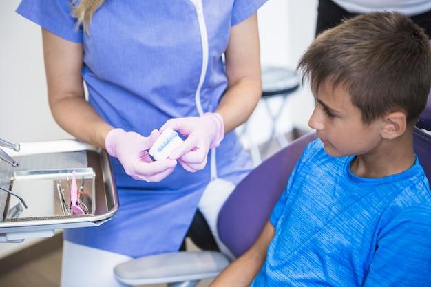 Weibliche zahnarzthand, die zahnputzform zum jungen in der klinik zeigt