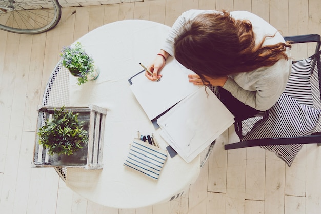 Weibliche zeichnungsskizze auf schreibtisch mit dem entwerfen der ausrüstung