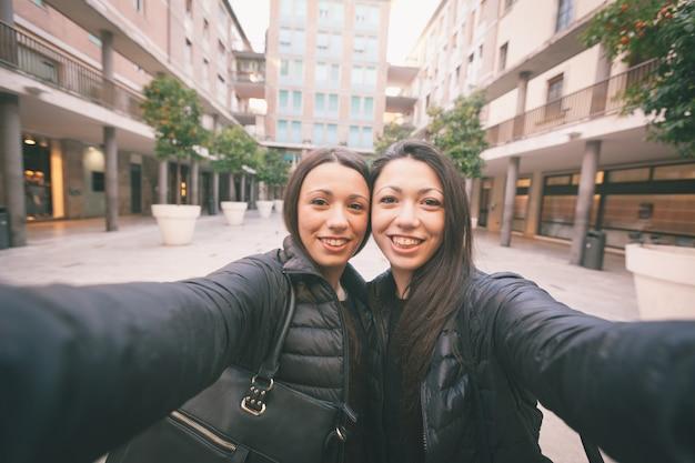 Weibliche zwillinge, die ein selfie in der stadt nehmen.