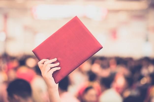 Weiblicher absolvent, der ein staffelungskleid trägt