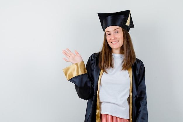 Weiblicher absolvent, der hand für die begrüßung in der uniform, in der freizeitkleidung und in der freudigen vorderansicht winkt.
