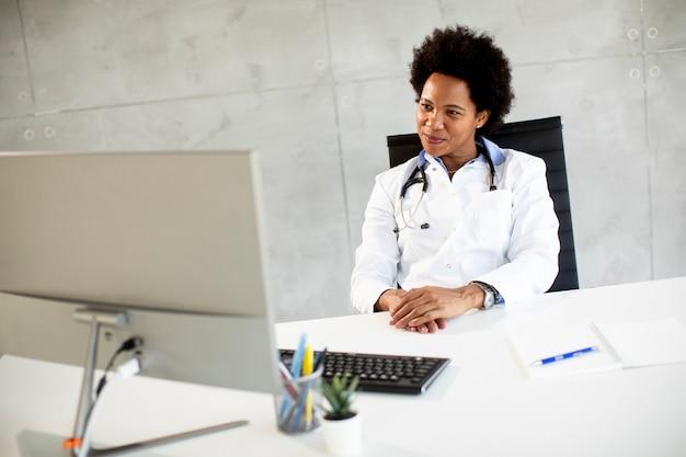 Weiblicher afroamerikanischer arzt, der weißen kittel mit stethoskop trägt, das hinter schreibtisch im büro sitzt