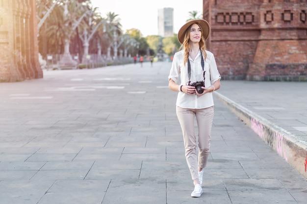 Weiblicher alleinreisender, der eine weinlesekamera beim gehen durch die stadt barcelona hält