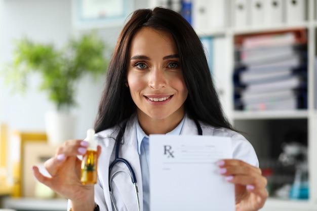 Weiblicher allgemeinarzt, der geduldigem tropfenzählerglas hanfkonzentratöl gibt