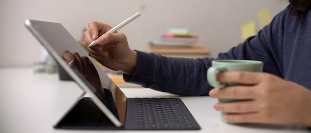 Weiblicher angestellter, der auf digitalem tablett mit stift schreibt und kaffeetasse auf schreibtisch hält
