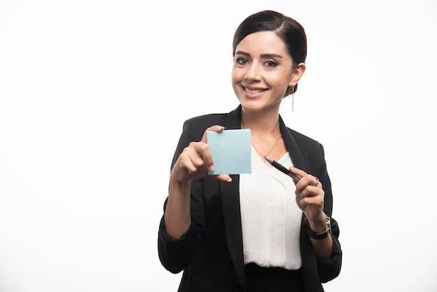 Weiblicher angestellter, der notizblock auf weißem hintergrund hält. foto in hoher qualität