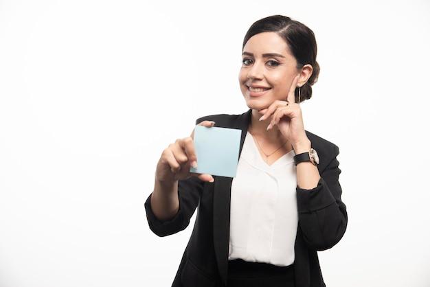 Weiblicher angestellter, der notizblock auf weißem hintergrund zeigt. foto in hoher qualität