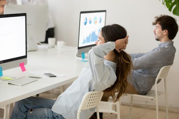 Weiblicher angestellter, der vom computerarbeitshändchen hinter kopf sich entspannt