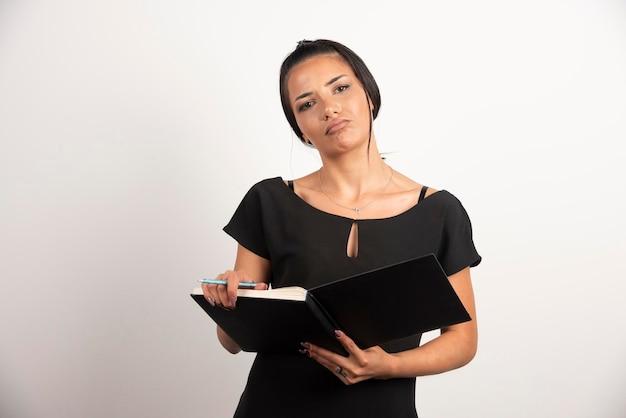 Weiblicher angestellter mit notizbuch, das auf weißer wand steht.
