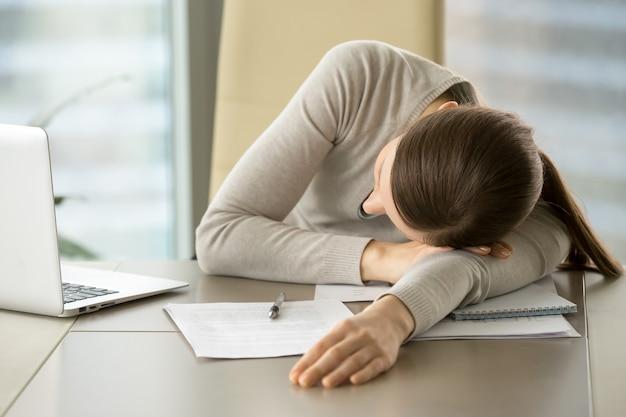 Weiblicher angestellter schlummert am arbeitsplatz im büro