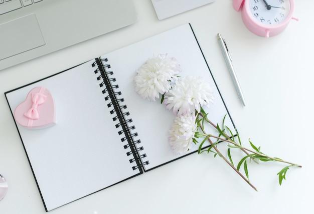 Weiblicher arbeitsbereich auf weißem tischnotizblock, bleistiftpflanzenwecker. draufsicht