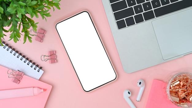 Weiblicher arbeitsplatz mit handy, laptop, kopfhörer, notizbuch und pflanze auf rosafarbenem pastellhintergrund.