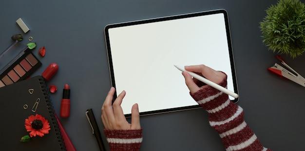 Weiblicher arbeitsplatz mit rotem luxuskonzept, draufsicht der frau arbeitend mit tablette