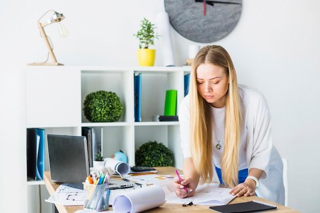 Weiblicher architekt, der an plan im büro arbeitet