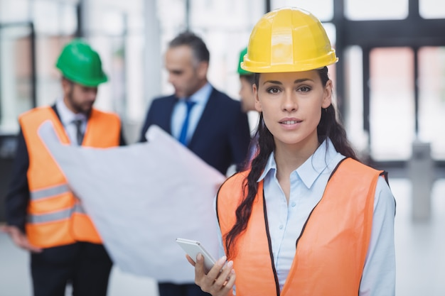 Weiblicher architekt, der handy hält