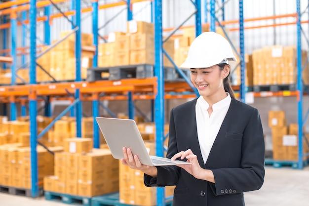 Weiblicher architekt, der laptop mit dem lächeln am lager hält. arbeitskonzept der leute.