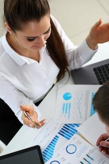 Weiblicher arm, der silbernen stiftpunkt im finanzdiagramm hält