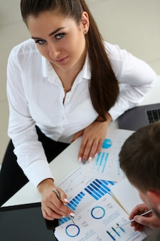 Weiblicher arm, der silbernen stiftpunkt im finanzgraphen hält