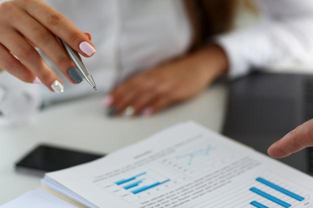 Weiblicher arm, der silbernen stiftpunkt in der finanzgrafik hält