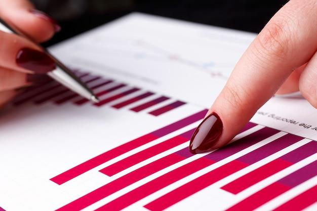 Weiblicher armgriff und silberner stift des punktes im finanzdiagramm