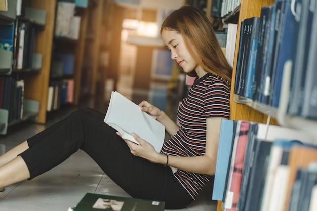 Weiblicher asiatischer student, der buch in der bibliothek studiert und liest
