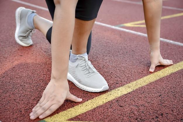 Weiblicher athlet auf startblöcken an der stadionsbahn, die für lauf sich vorbereitet.