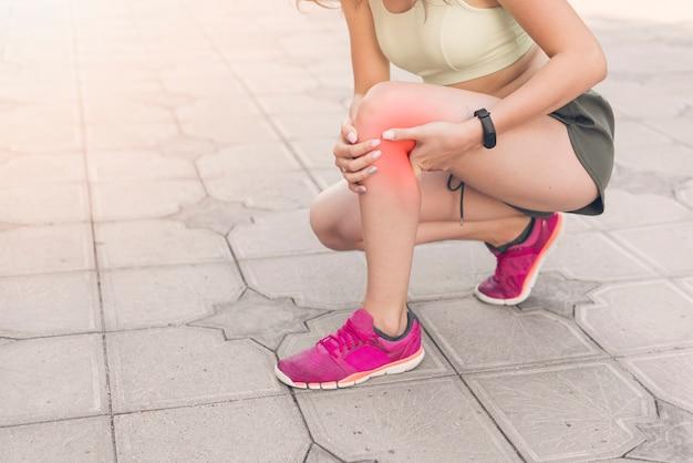 Weiblicher athlet, der auf der pflasterung hat schmerz im knie sich duckt