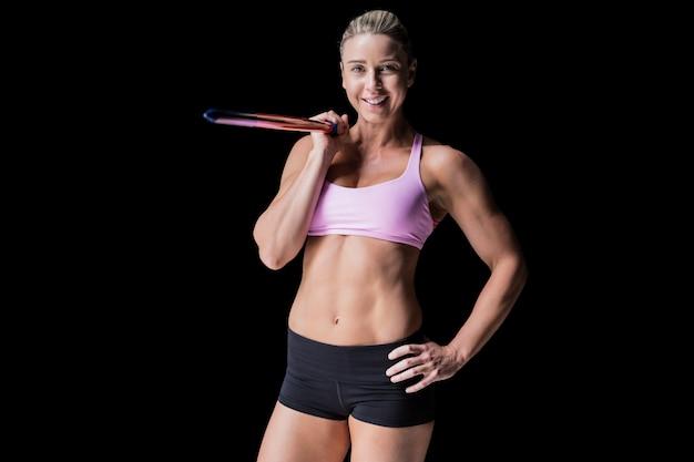Weiblicher athlet, der einen speer auf schwarzem hält