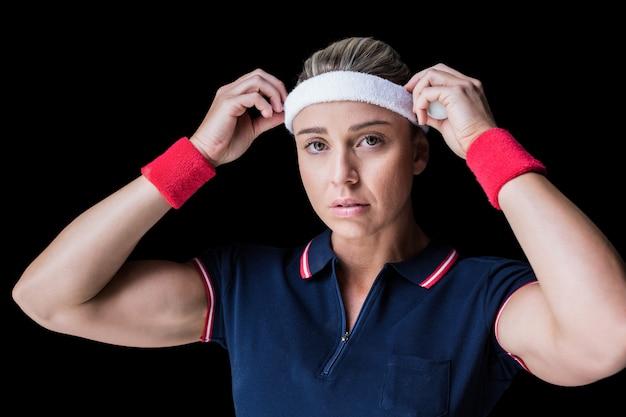 Weiblicher athlet, der ihr stirnband auf schwarzem justiert
