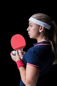 Weiblicher athlet, der klingeln pong auf schwarzem spielt