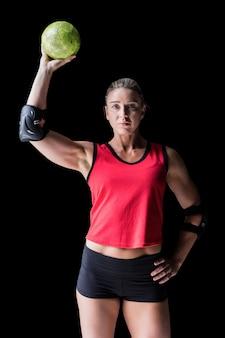 Weiblicher athlet mit dem ellbogenschützer, der handball auf schwarzem hält