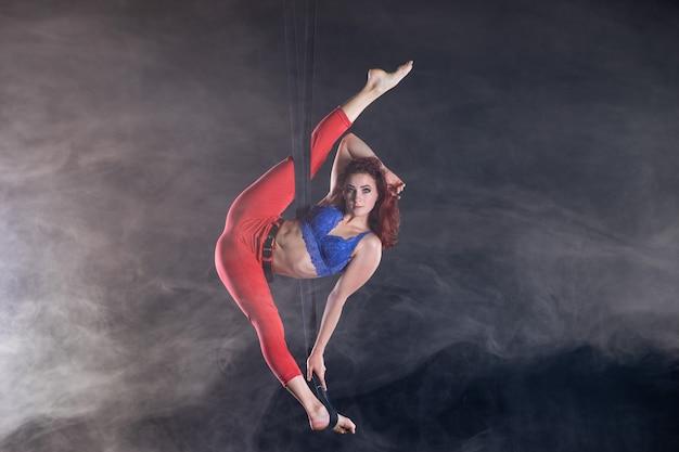 Weiblicher athletischer sexy flexibler luftzirkuskünstler, der auf der seide tanzt