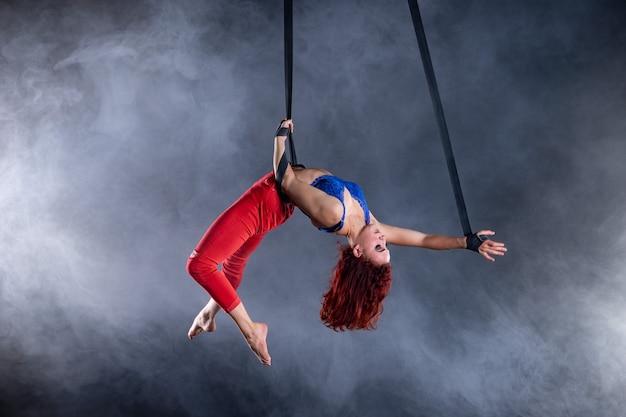 Weiblicher athletischer, sexy und flexibler luftzirkuskünstler mit rotschopf auf luftriemen auf schwarzem hintergrund.