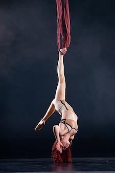 Weiblicher athletischer, sexy und flexibler luftzirkuskünstler mit rotschopf, der auf der seide in der luft tanzt.