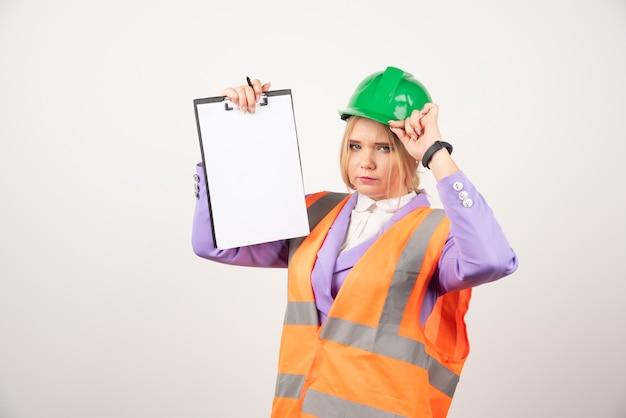 Weiblicher auftragnehmer mit grünem helm, der klemmbrett auf weißer wand hält.